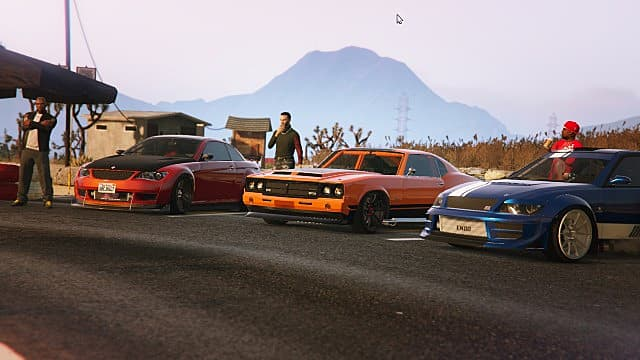 A car meet in the desert in GTA Online with three sports cars.