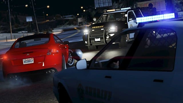 A police SUV and patrol car stop a red sports car.