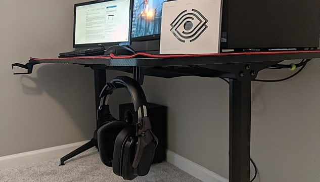 An angled shot of the ergonomic desk, showing the headset hook and headset, cupholder, monitors.