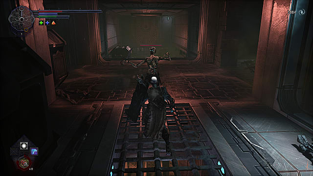 The spawn using a shield to knock back a thin, decaying enemy in a red-lit, metal corridor.