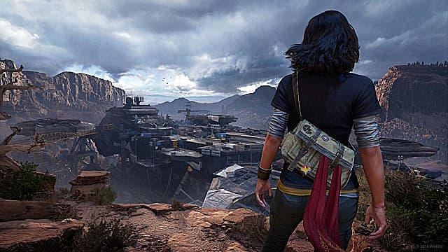 Kamala Khan standing on a desert cliff overlooking a large complex below, with cliffs and dark clouds in the distance.