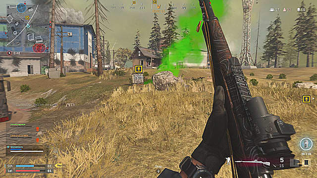 A player holding a marksman rifle up, looking at the green smoke of a skull crate on the edge of a grassy hill.