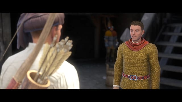 The robber baron, with short hair and sporting a gold shirt with red belt, talks to the player inside a fort in Kingdom Come Deliverance