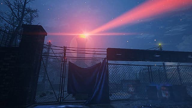 Player looking at a lighthouse emitting red light behind a tall chain-link fence.