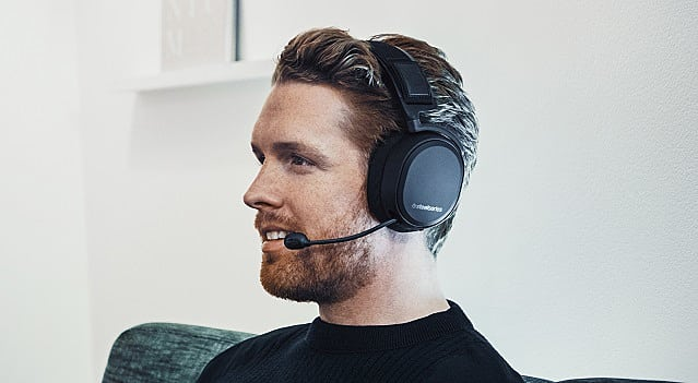 Man in black shirt wears Arctis Pro Wireless while sitting on couch