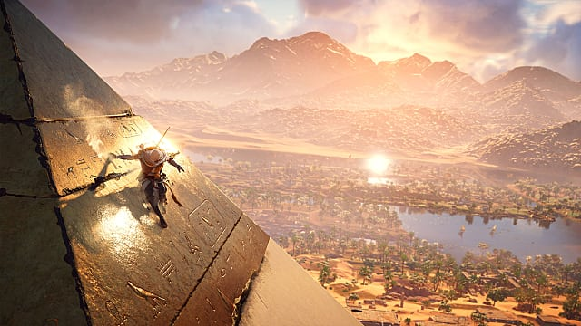 Bayek scaling a pyramid in AC:O