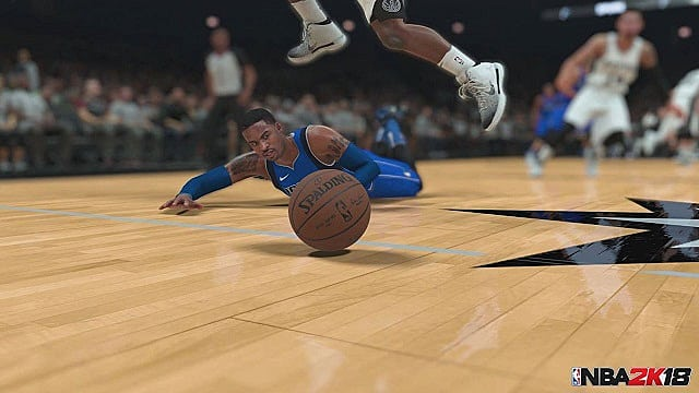 A basketball player dives for a ball on the hardwood as another player jumps