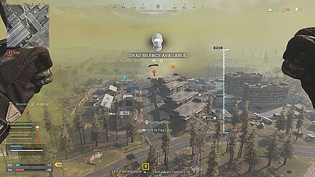 A player parachuting into the map over a grove of trees and buildings, tagging other players.