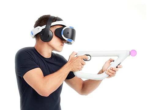 a man wearing a black shirt wears a PSVR and wields a gun peripheral with two Move controllers attached to it