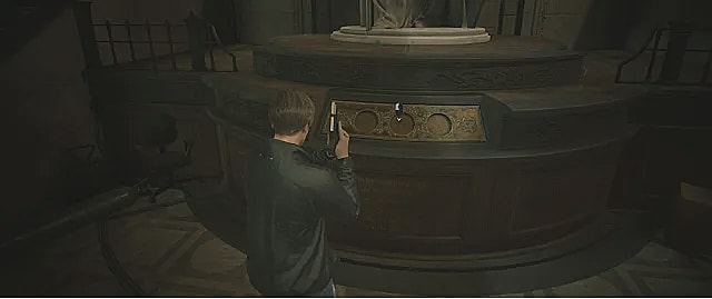 Leon stands in front of the medallion puzzle in the RPD.