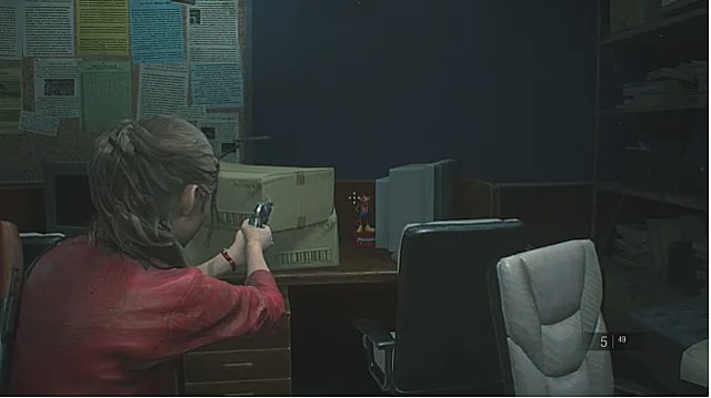 Calire aims gun at statue next to computer monitor.