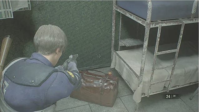 Leon aim his gun at a Mr. Raccoon that sits behind some luggage.