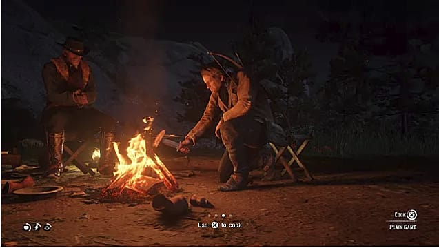 Arthur Morgan cooks meat over a fire at a campsite in Red Dead Redemption 2
