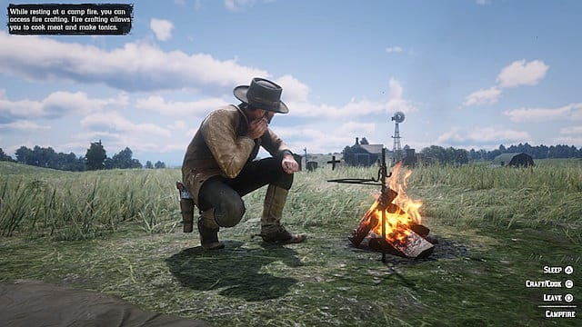 Arthur kneels next to a campfire in a field near a farmhouse in RDR2