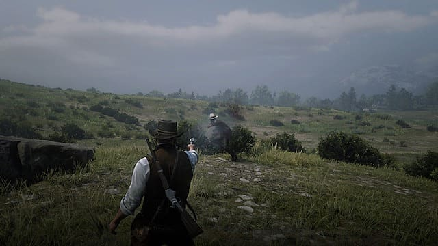 Arthur Morgan shoots a bandit with a Cattleman Revolver on a grassy knoll
