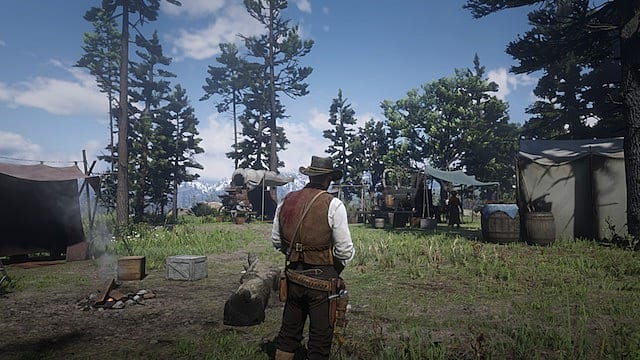 Arthur Morgan, with a bloody shoulder, looks out at the Horseshoe Overlook camp next to a fire