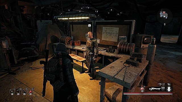 A cloaked player looking at Rigs, a tall, bald man in blacksmith's clothes in a workshop.
