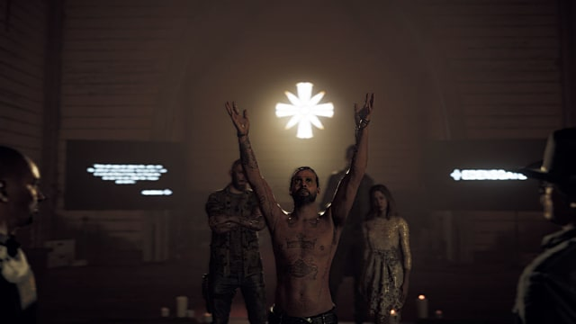 A shirtless cult leader stands with his arms raised to the heavens as followers look on in Far Cry 5