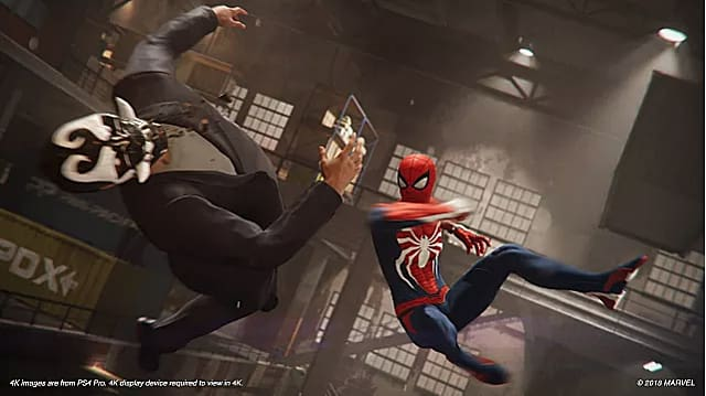 Spiderman jumps to punch a bad guy in the face in a warehouse