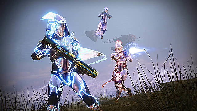 A Warlock floats behind a glowing blue Hunter and a Titan shooting.