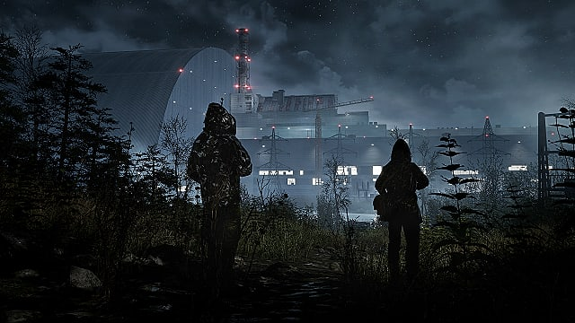 Two soldiers in camouflage looking toward a powerplant at night.
