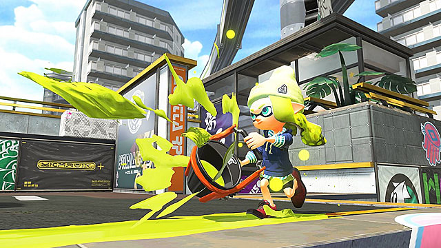 An inkling for the yellow team using a slosher