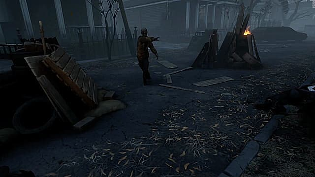 A zombie walking down a dark street towards a barrel fire in The Walking Dead: Saints & Sinners
