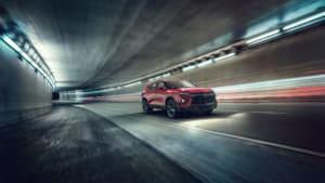 a red Chevrolet Blazer cruising through a tunnel.
