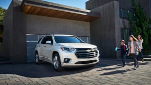 A white 2020 Chevrolet Traverse standing on a driveway with a family approaching.