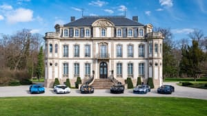 A massive lineup of Bugattis in-front of a mansion
