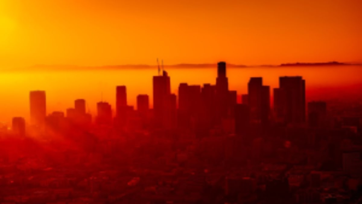 The Los Angeles skyline, with a setting sun just off to the left creating an orange glow across the city of angels