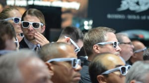 journalists at the 2012 L.A. Auto Show wearing polarized sunglasses to see a Volkswagen exhibit.
