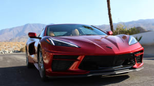 The front of a red 2021 Chevrolet Corvette Stingray, with the Palm Springs desert landscape in the background.