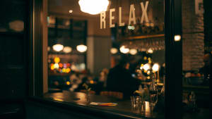 """a bar with a sign saying """"relax"""" hanging above."""