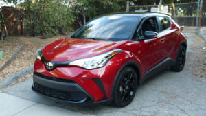 exterior front and left side of a red 2021 Toyota CH-R Nightshade parked on a driveway