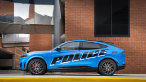 a blue Ford Mach E police car on the street, with a brick building in the background.