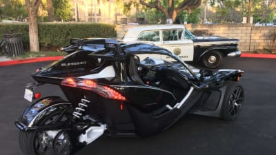 rear of the Polaris Slingshot with a classic police cruiser in the background
