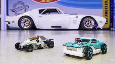 two diecast Hot Wheels models on the floor with a life-size Legends vehicle with the Hot Wheels logo in the background.