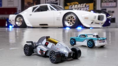 the diecast Hot Wheels models on the floor with a life-size Legends vehicle in the background.