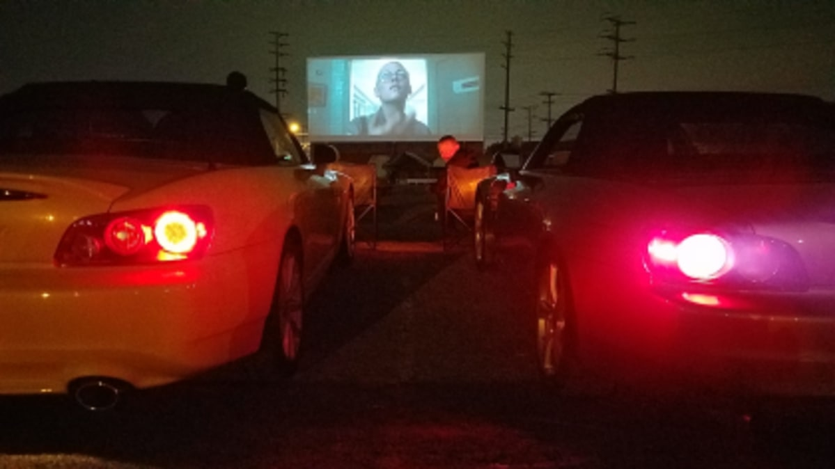 Two sports cars next to each other at a drive-in movie.