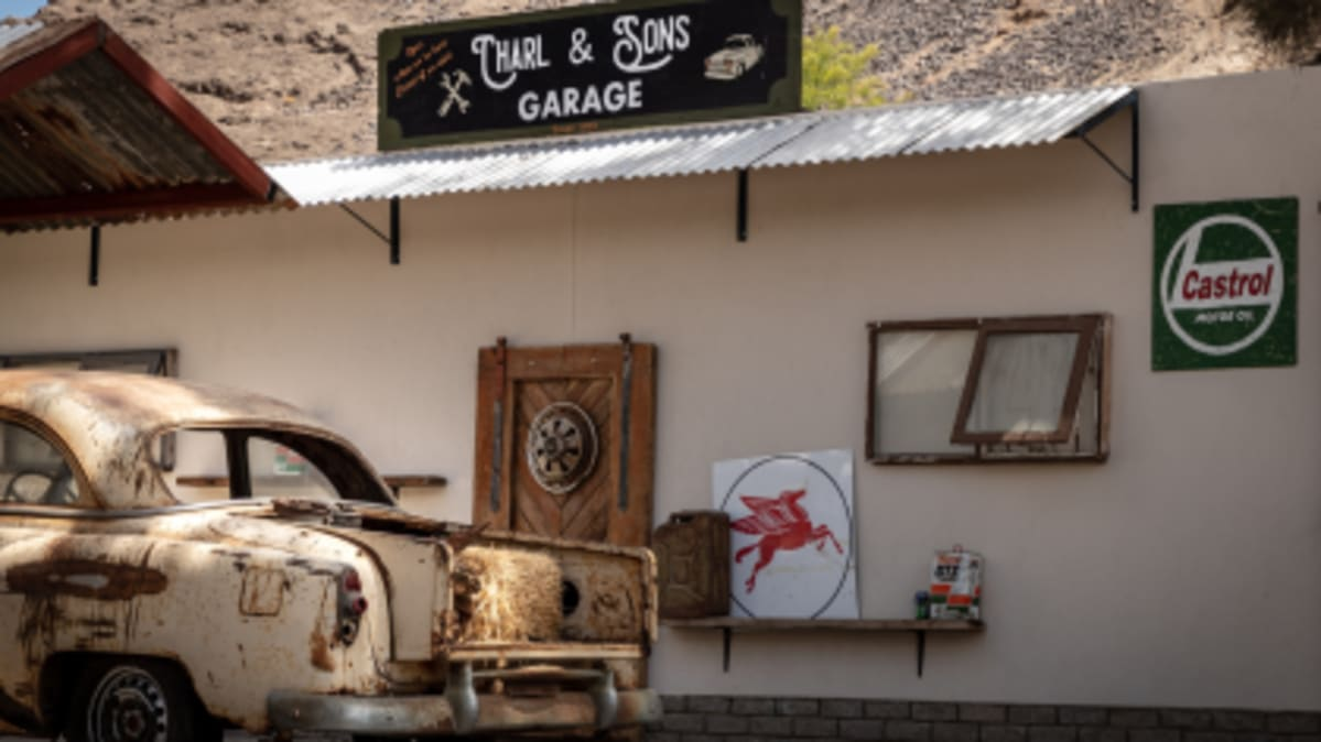 a garage sign on the roof of a rustic workshop, with a rusty car in the foreground.
