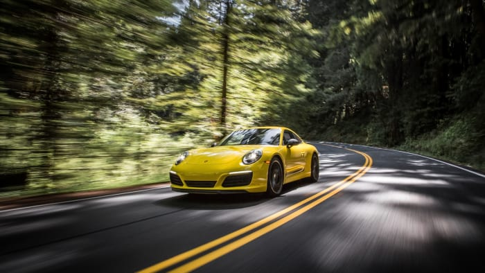 Yellow Porsche 911 driving on road
