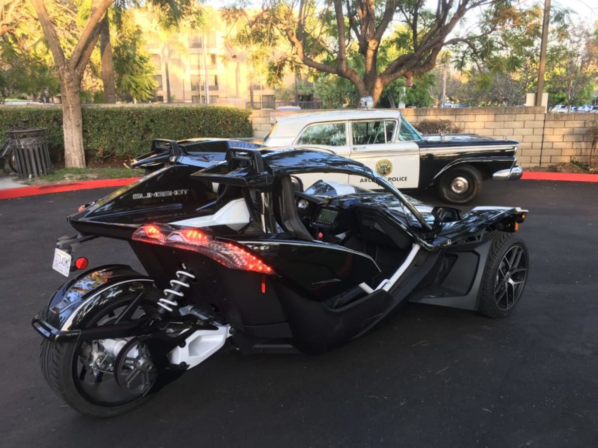 Polaris Slingshot Grand Touring beside a police car
