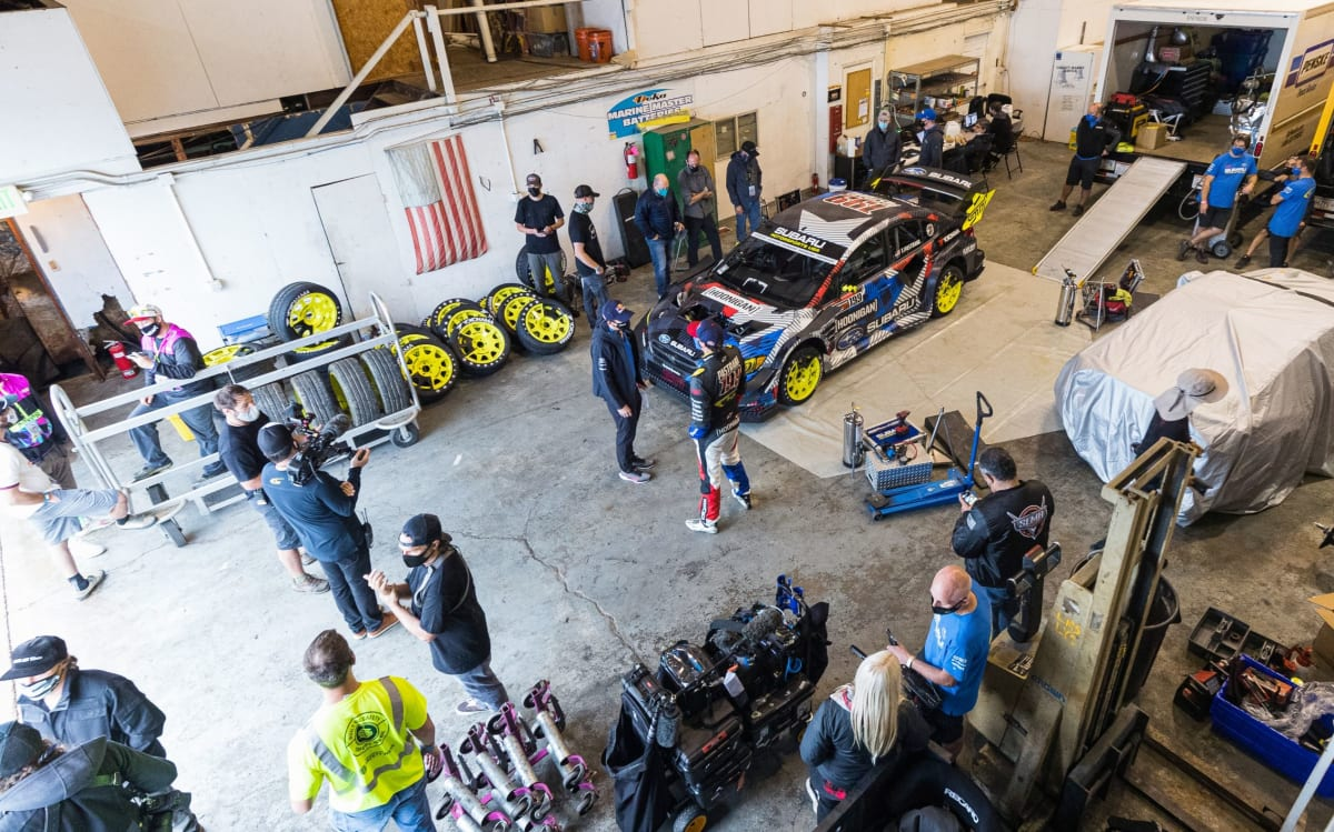 the gymkhana team in the garage with the gymkhana car