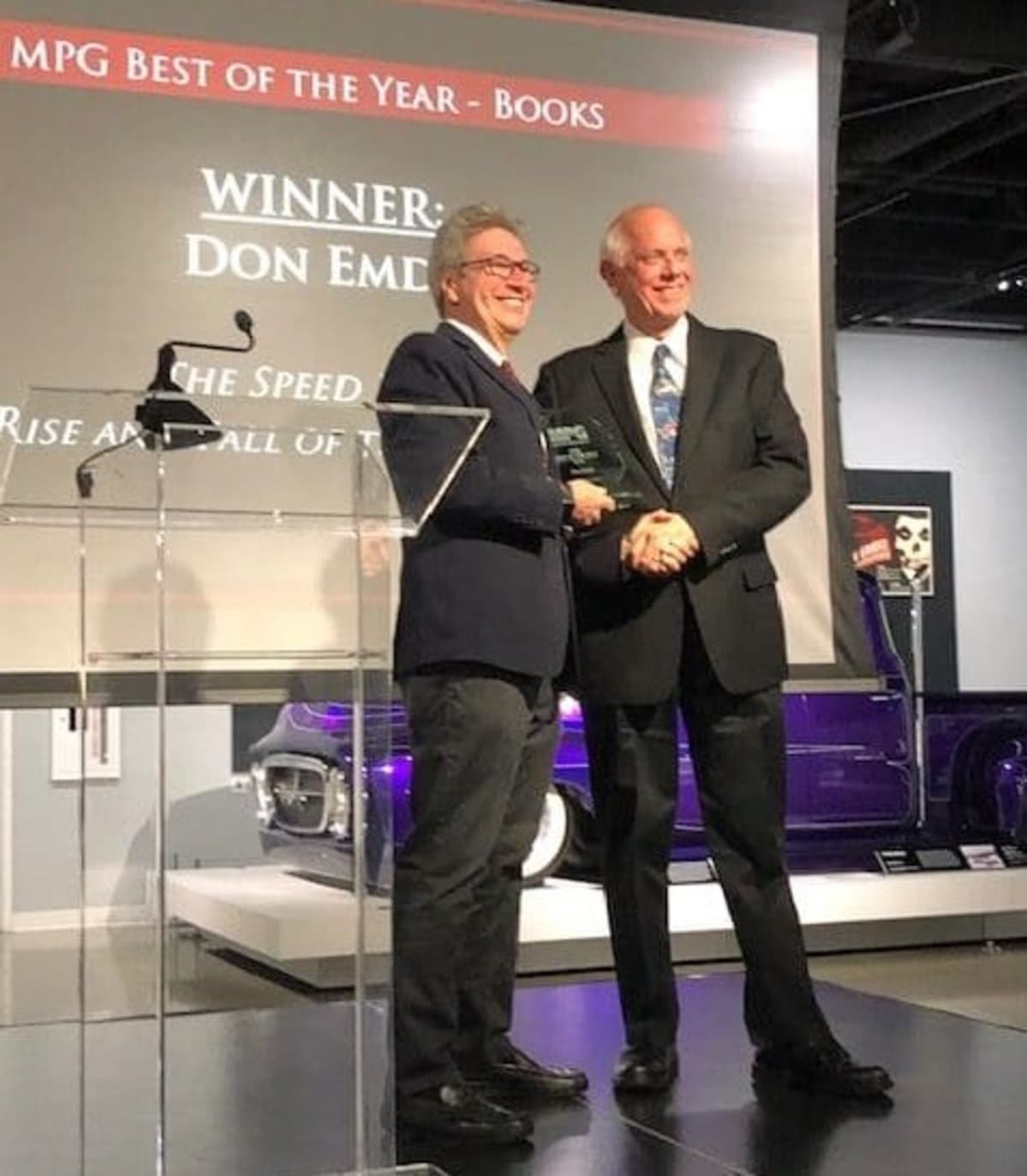 "Don Taylor, one of the 2019 Motor Press Guild 'Best Book' committee judges, awards Don Emde First Place for ""The Speed Kings: The Rise and Fall of the Motordromes""."