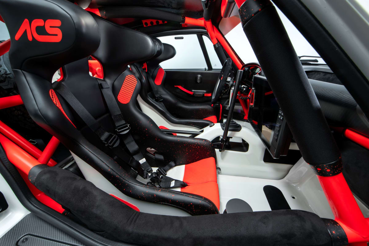 View from co-driver's door showing driving environment with FIA specification race seats.