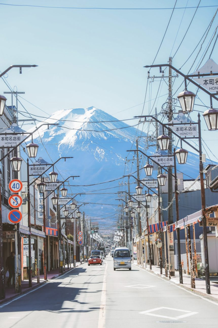busy Japanese street with huge snow-capped mountain in the background