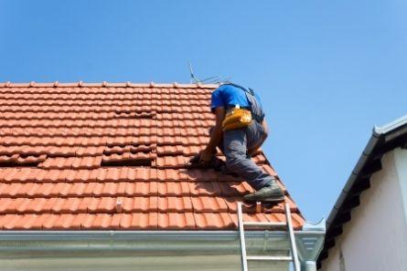 Bilde viser mann som arbeider på tak.
