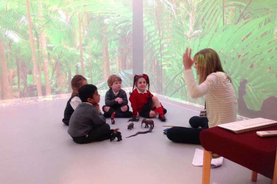 Kindergarten teacher using the sensory room with a rain forest backdrop