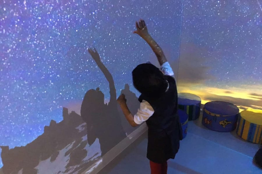 Kindergarten pupil using the sensory room on a night scene with stars.